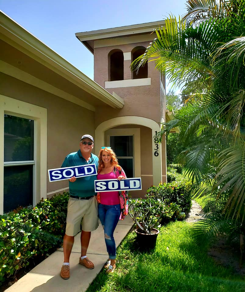 couple with sold sign in front of house